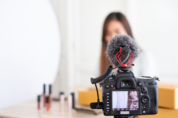 Selective focus at camera ,Asian blogger recording video and  setting light for review unpacking cosmetic and make up  at home studio,influencer social media.