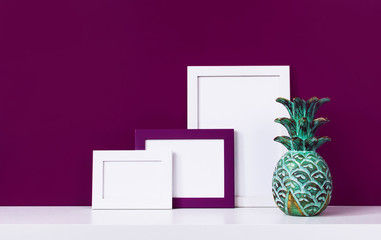 Wooden empty frames for a photo and a wooden emerald pineapple on a white shelf on a background of a bright purple red wall. Blank paper frames, modern home decor mock-up. Interior background.