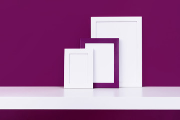 Three wooden empty frames for a photo on a white shelf on a background of a bright purple red wall. Blank paper frames, modern home decor mock-up.