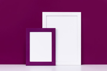 Two wooden empty frames for a photo on a white shelf on a background of a bright purple red wall. Blank paper frames, modern home decor mock-up.