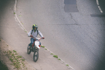 A young guy is riding a motorcycle on the sidewalk