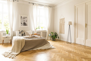 Blanket on bed with wooden tray in spacious bright bedroom interior with poster. Real photo Wall mural
