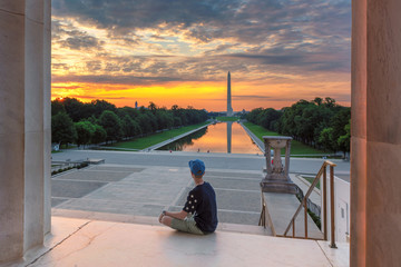 Teenager meets dawn at the Lincoln Memorial in morning summertime. Washington Monument Sunrise from Lincoln Memorial, Washington DC, USA.
