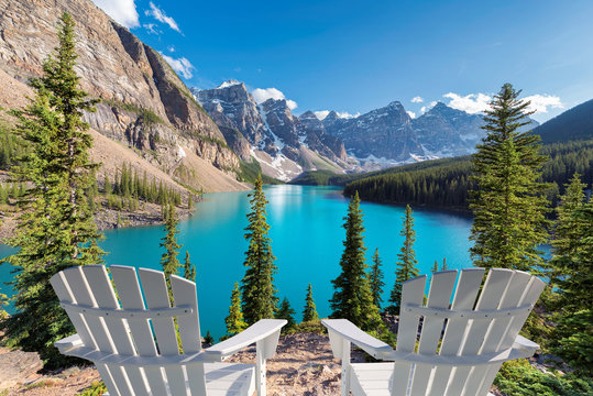 Beautiful turquoise waters of the Moraine Lake at sunset with snow-covered peaks above it in Rocky Mountains, Banff National Park, Canada.