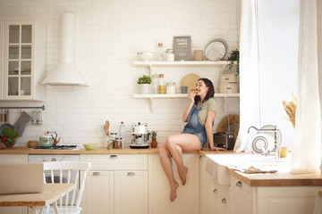 Portrait of cute brunette girl eating delicious pastry, sitting alone on counter in modern kitchen interior. Playful funny barefooted young female with dark hair having doughnut for breakfast