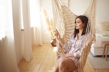Beautiful young dark haired female in trendy striped nightwear relaxing in swing. Attractive brunette chubby girl wearing silk pajamas swinging in woven chair at home by large window, daydreaming