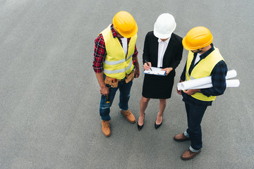 overhead view of female architect and male workers in hardhats working with clipboard and blueprints