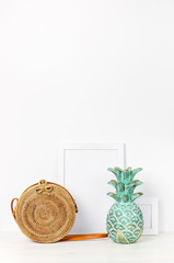 Wooden empty frames for a photo, wooden emerald pineapple, fashionable handmade natural organic rattan bag on a background of a white wall. Blank paper frames, accessories in the house, modern home