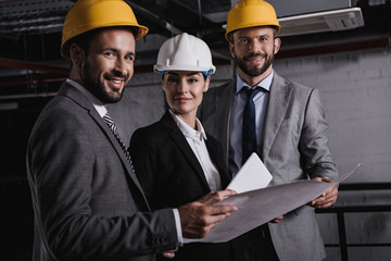 architects in suits and helmets working with blueprint and digital tablet on construction together
