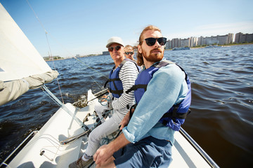 Foto auf Acrylglas Segeln Serious calm men in life jackets and sunglasses sitting in row on yacht and looking around during sailing tour on river