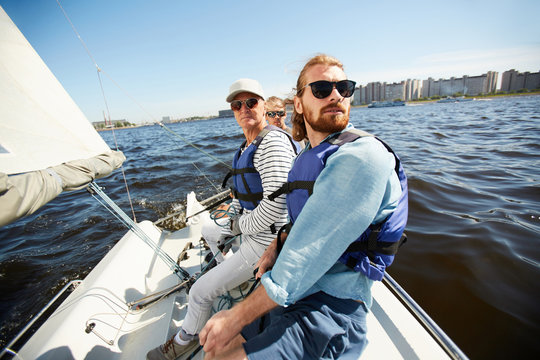 Serious calm men in life jackets and sunglasses sitting in row on yacht and looking around during sailing tour on river