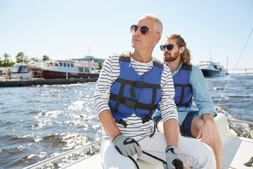 Serious relaxed tourists in fashionable sunglasses and life jackets looking around while sitting on sailboat deck during sailing tour