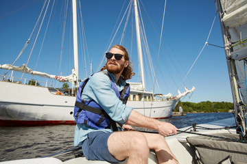 Serious carefree young bearded man in sunglasses operating sail with rope and looking around during sailing travel