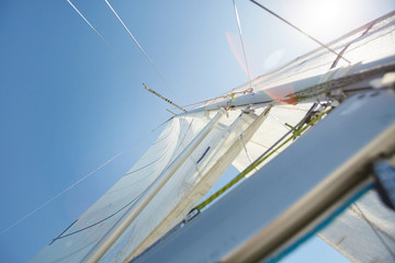 Below view of white sail with ropes used to propel boat with wind, sunlight effect