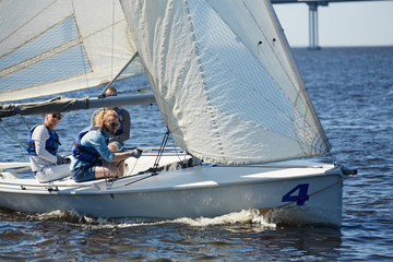 Skilled handsome men participating in sailing competition: hipster young man handling sailboat using rope to direct mainsail on river
