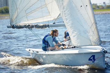 Serious handsome professional yachtsman using rope to direct sailboat while participating in sport competition together with assistant