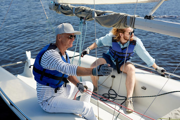 Serious father and son wearing life jackets holding ropes while handling sailboat together: they sitting on yacht deck and looking around