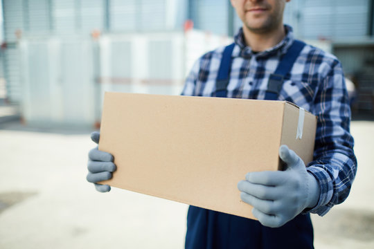Close-up of moving company worker in gloves holding cardboard box and carrying it at container storage area