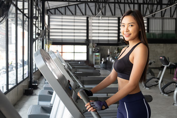 Asian woman Attractive young sports woman is working out in gym. Doing cardio training on treadmill. Running on treadmill.