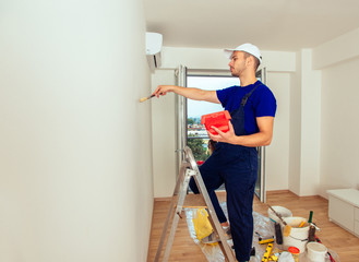Young Painter In Blue Uniform Painting With Paintbrush On Wall. Home renovation and decoration concept.