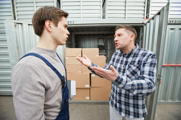 Displeased young male client in casual shirt scolding container storage worker and gesturing while blaming him, they standing near open full container