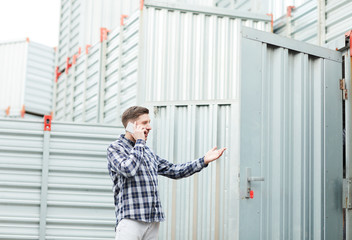 Young container owner in casual clothing using mobile phone while calling manager and gesturing when explaining his problem