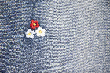 Flower embroidery on denim jeans texture background