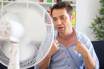 Man refreshing with electric fan against summer heat wave Wall mural