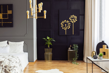 Black and gold poster above plants in bedroom interior with white pillows on bed. Real photo