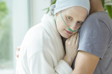 Weak woman with cancer hugging husband during chemotherapy