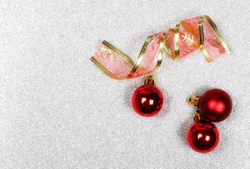 Decorative red balls and ribbon, Christmas ornaments isolated on glittering, silver background, top view