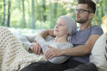Boyfriend supporting sick girl with breast cancer while relaxing at home