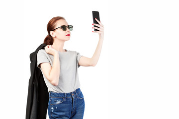 Portrait of a young attractive woman making selfie photo on smartphone isolated on a white background