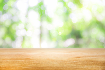 Wooden table top with green natural with sunshine background for your product presentation.