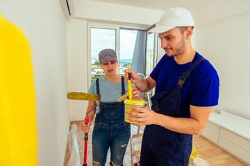 Young cheerful couple painting wall at home with paint stick roller. Young family renovating their new apartment concept.