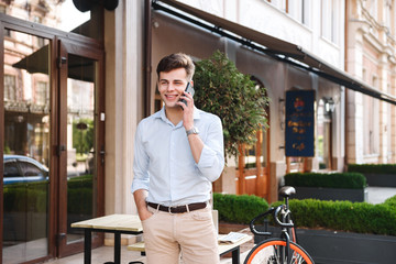 Smiling young stylish man in shirt talking on mobile phone