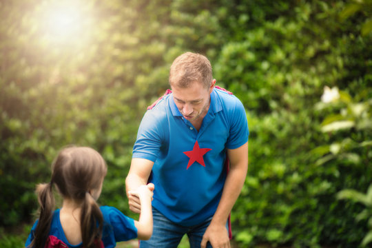 Young daddy and cute little girl in a superhero's costumes playing together at park on weekend. Superdad concept.