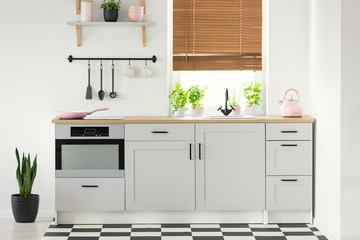 Real photo of a kitchen interior with white cupboards, pink accessories, plants and window blinds