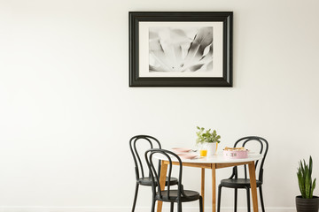 Real photo of a laid dining table with black chairs and painting on an empty wall. Place your graphic