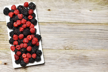Mixed forest fruits as blackberry and raspberry on rectangular white plate, isolated on rustic wooden background