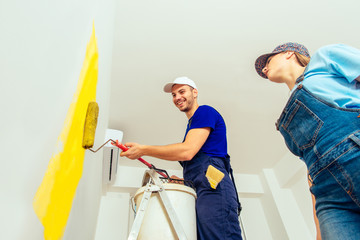 Man standing on scale painting walls with yellow color. Young family renovating their new apartment concept.