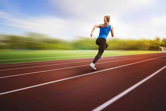 beautiful young female athlete running on running track back view on blur background. An athlete runs around the stadium jumping photo in flight. Athletics