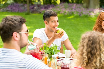 Happy hispanic man eating an apple during a meeting with his friends on the patio