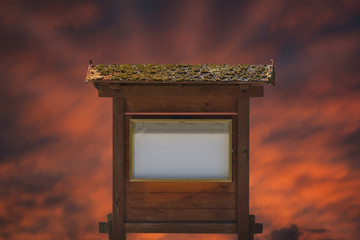 Free space for an inscription or image on an old wooden billboard against the backdrop of the setting sun.
