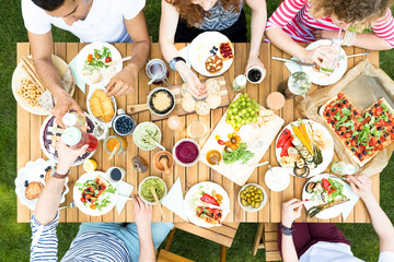High angle of a group of people sitting around a wooden table talking, toasting with colorful drinks and eating vegetarian food