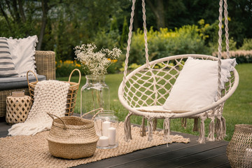Pillow on hanging chair and basket on carpet in the garden during spring