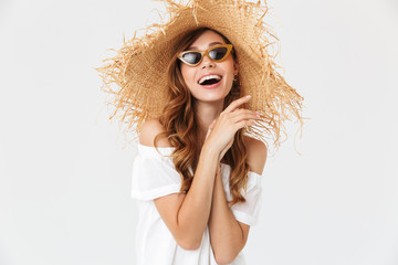 Portrait of modern cute woman 20s wearing big straw hat and sunglasses posing on camera with happy smile, isolated over white background