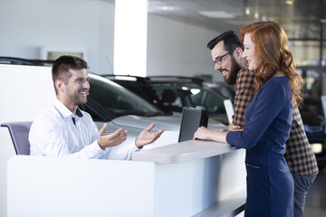 Smiling car seller talking with happy buyers in exclusive showroom