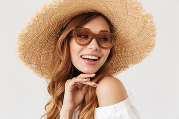Image of fashion cute woman 20s wearing big straw hat and sunglasses posing on camera with happy smile, isolated over white background