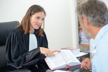 Lawyer showing text from book to client